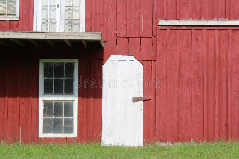 O vermelho pintou o celeiro com guarnição branca da porta e da janela fotos de stock