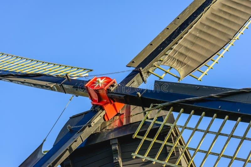O vermelho pintou a cruz do moinho de vento com as velas do fim imagem de stock royalty free