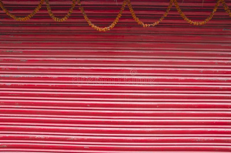 O vermelho pintou porta ondulada do metal e floresce a festão fotografia de stock