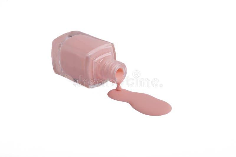 O verniz para as unhas cor-de-rosa é derramado da garrafa na tabela em um fundo branco imagens de stock