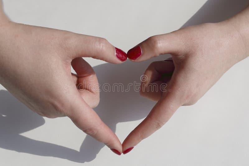 O verniz para as unhas vermelho pintado à mão de mulher elegante, mãos faz uma forma do coração imagem de stock royalty free