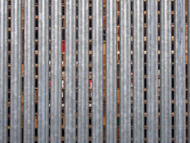 O vertical galvanizou a cerca de aço com as páletes de madeira no armazenamento exterior visível entre as diferenças foto de stock