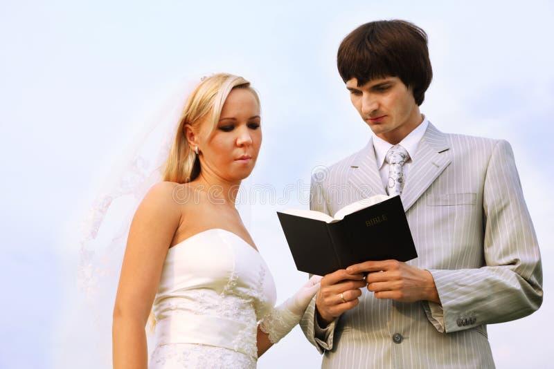 O vestido branco desgastando do noivo e da noiva leu a Bíblia fotos de stock