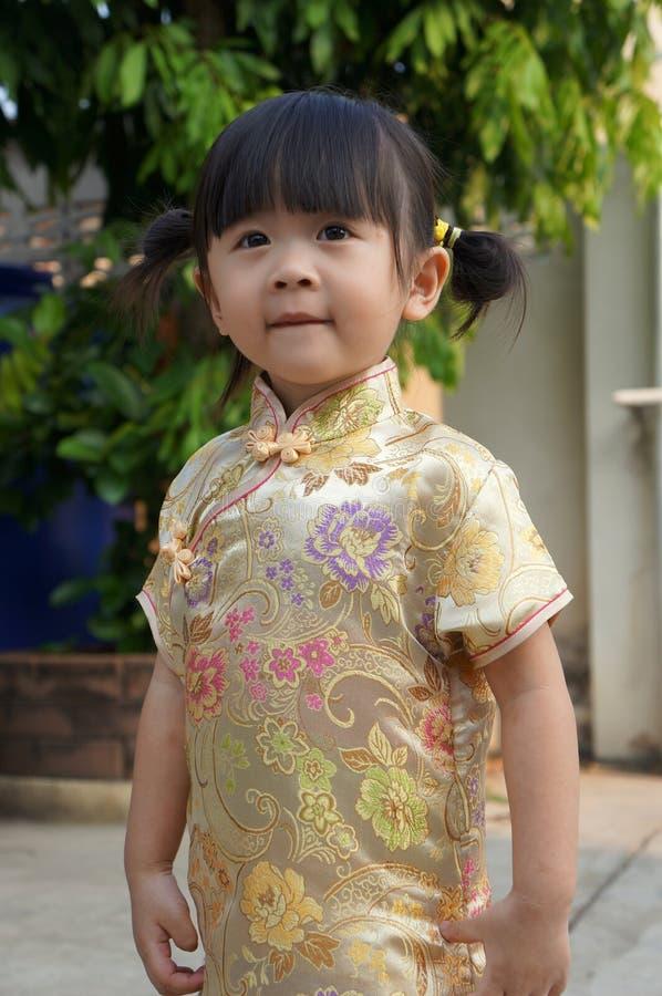 O vestido chinês do ouro, fecha-se acima da menina asiática pequena feliz no vestido tradicional chinês Ano novo chinês feliz imagem de stock