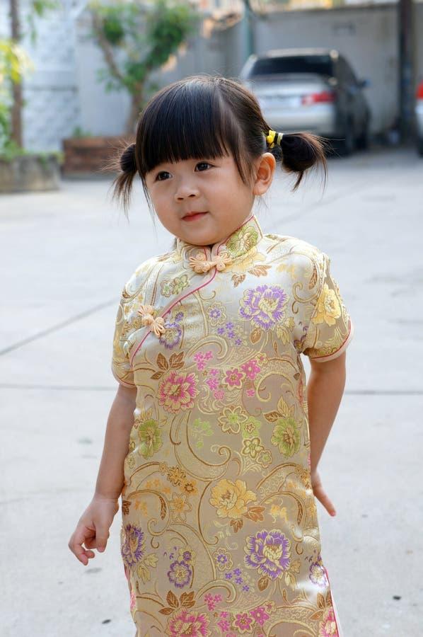 O vestido chinês do ouro, fecha-se acima da menina asiática pequena feliz no vestido tradicional chinês Ano novo chinês feliz foto de stock royalty free