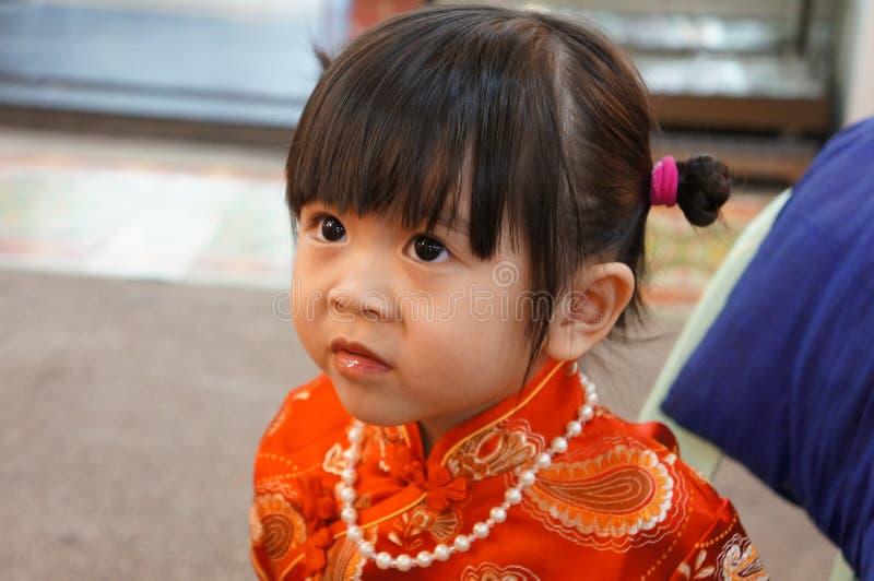 O vestido chinês vermelho, fecha-se acima da menina asiática pequena feliz no vestido tradicional chinês Ano novo chinês feliz imagens de stock