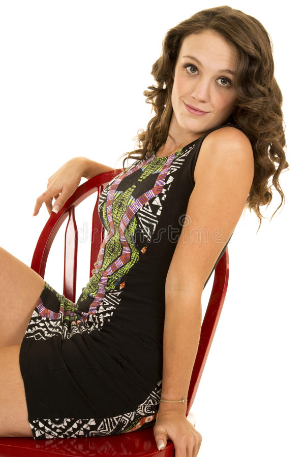 O vestido curto da mulher senta a cadeira vermelha inclina-se para trás fotografia de stock royalty free