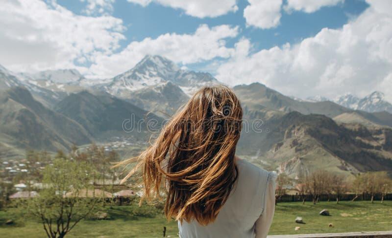O vestido da menina atrás do verão olha picos da neve das montanhas fotos de stock