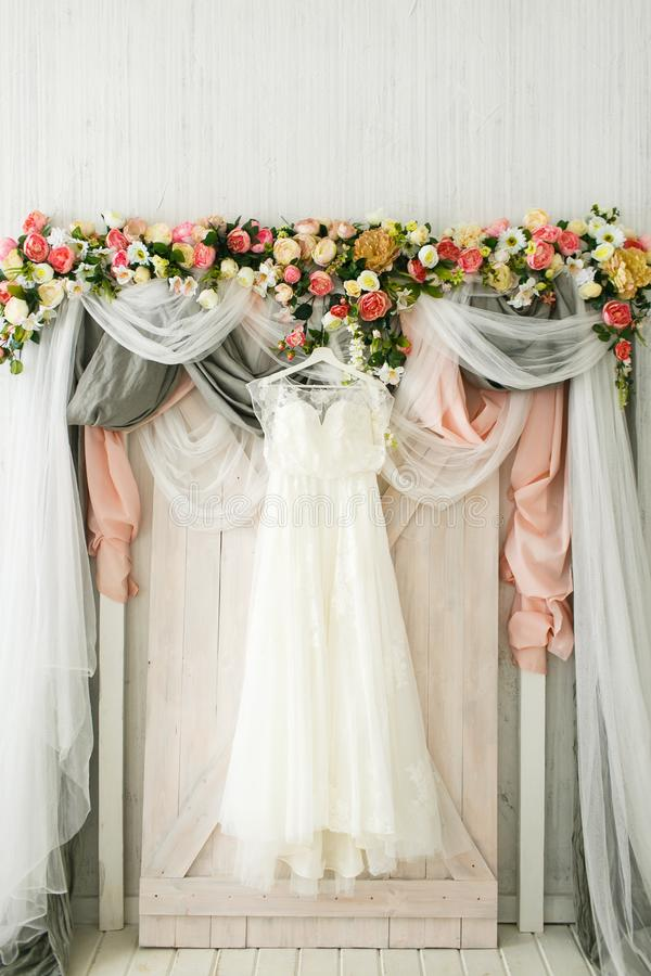 O vestido da noiva pendura em um arco do casamento fotos de stock