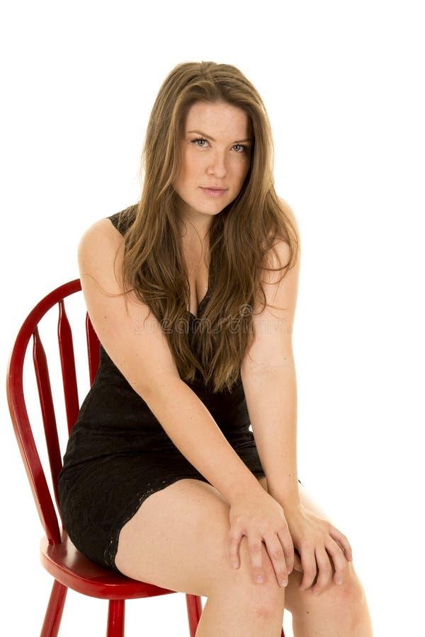 O vestido do preto da mulher senta-se nas mãos da cadeira no sorriso dos joelhos imagem de stock royalty free