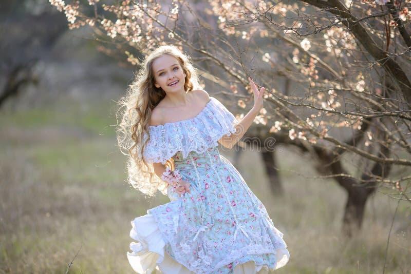 O vestido feliz da menina corre em um jardim de florescência para amar imagem de stock royalty free