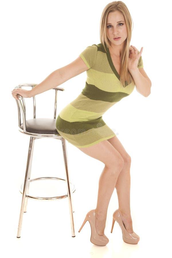 O vestido verde da listra da mulher senta-se mal na cadeira foto de stock