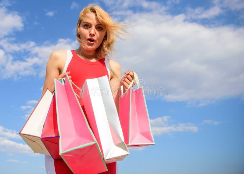 O vestido vermelho da mulher leva o fundo do céu azul dos sacos de compras do grupo Menina satisfeita com as compras Melhor manei fotos de stock