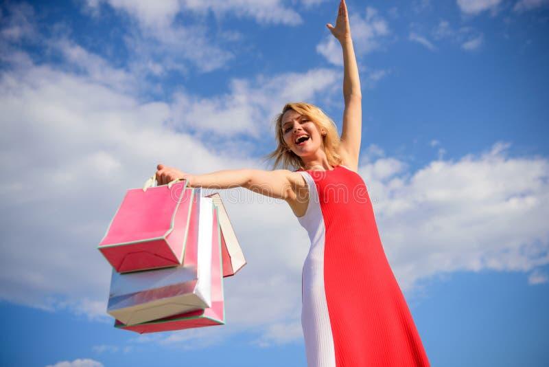 O vestido vermelho da mulher leva o fundo do céu azul dos sacos de compras do grupo Sinta a compra livre tudo você querer Comprad foto de stock royalty free