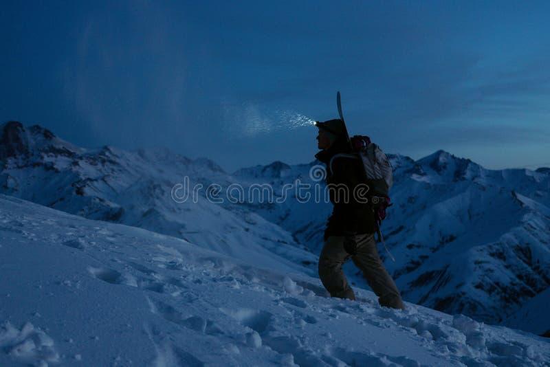 O viajante corajoso ilumina a maneira com um farol na montanha do inverno da noite Snowboarder com trouxa e um snowboard atrás do fotos de stock royalty free
