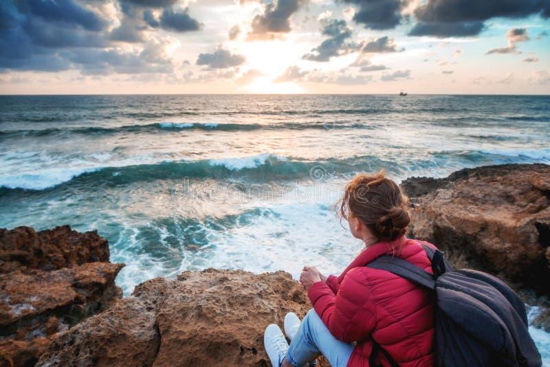 O viajante da jovem mulher senta-se na costa do mar e do wat do inverno fotos de stock royalty free