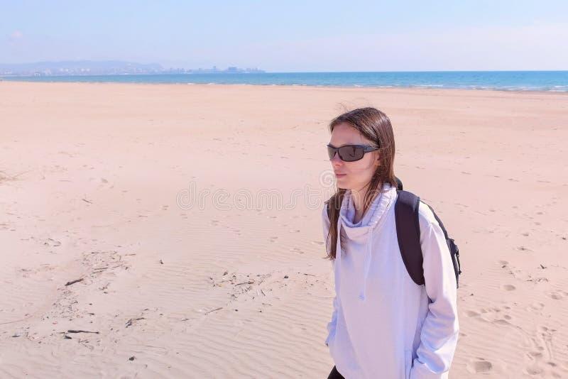 O viajante da menina anda na estação baixa vazia da praia da areia do mar nas dunas em férias fotografia de stock