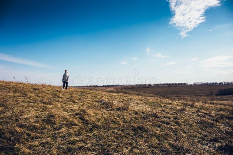 O viajante da mulher com trouxa vai em montes da montanha no fundo dramático do céu, conceito do curso, espaço da cópia foto de stock
