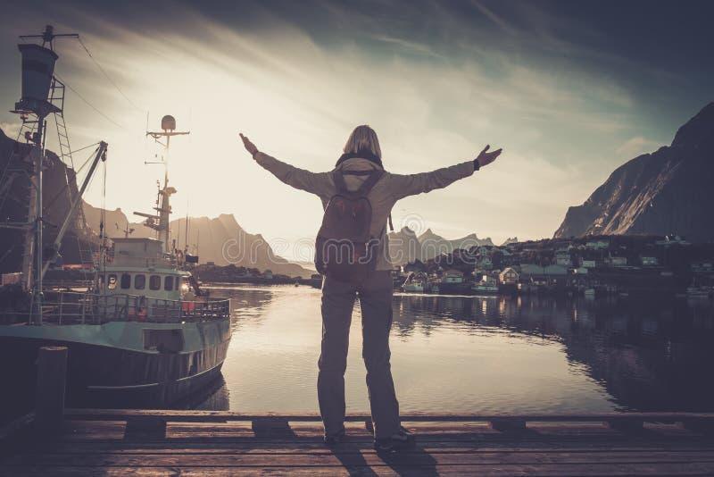 O viajante da mulher na vila de Reine com os braços largos abre foto de stock royalty free