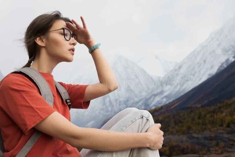 O viajante da mulher olha na distância nas montanhas nevados Roupa do verão e uma trouxa nos ombros fotos de stock