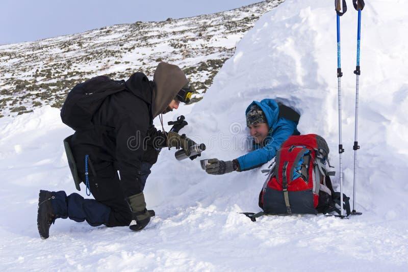 O viajante derrama o chá de sua garrafa térmica a seu amigo que senta-se em um iglu nevado da casa fotos de stock royalty free
