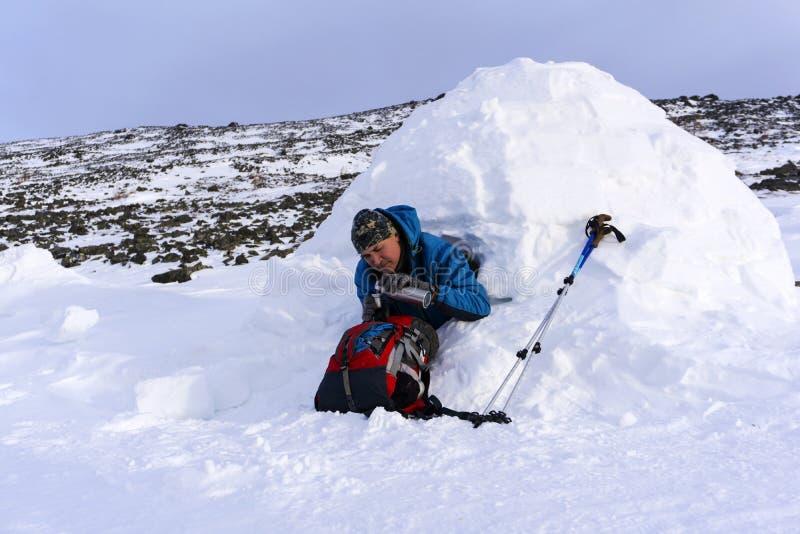 O viajante derrama-se uma bebida quente de uma garrafa térmica, sentando-se em um iglu nevado da casa foto de stock