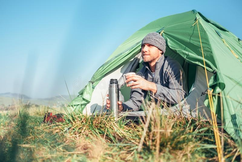 O viajante do homem acordou acima na barraca e bebe o chá quente imagens de stock
