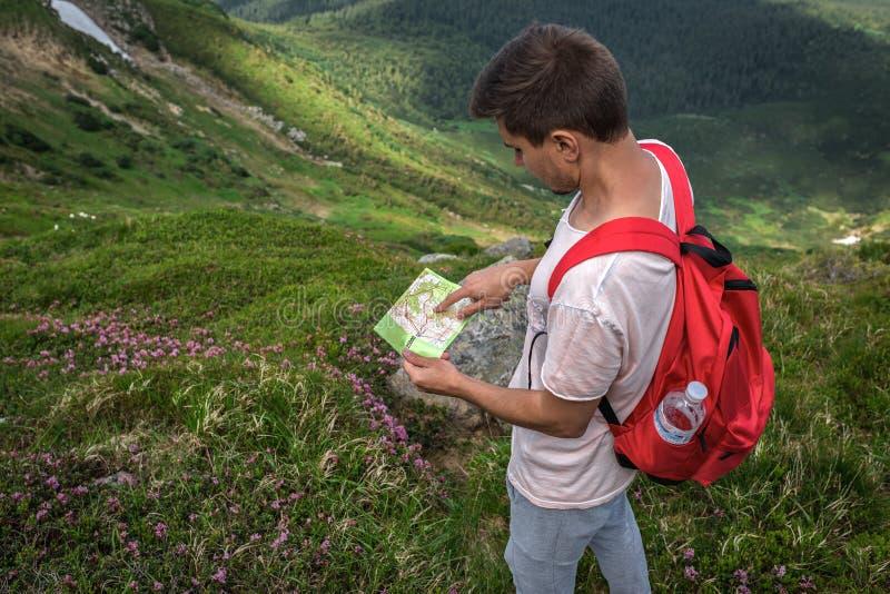 O viajante do homem do indivíduo com a trouxa vermelha perdida na montanha guarda o mapa Caminhando o verão exterior fotos de stock royalty free