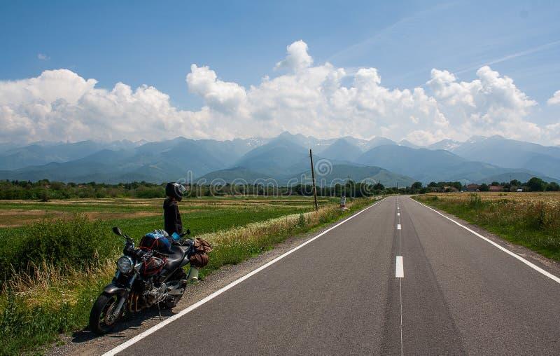 O viajante do motociclista da jovem mulher olha as montanhas Transfagarasan Romênia fotografia de stock royalty free