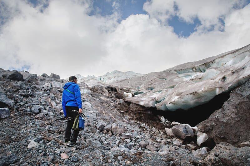 O viajante em um tampão e em óculos de sol está estando nas montanhas nevados na geleira Viajante em um ambiente natural imagens de stock