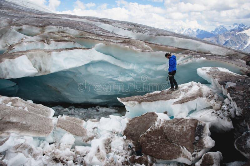 O viajante em um tampão e em óculos de sol está estando nas montanhas nevados na geleira Viajante em um ambiente natural foto de stock