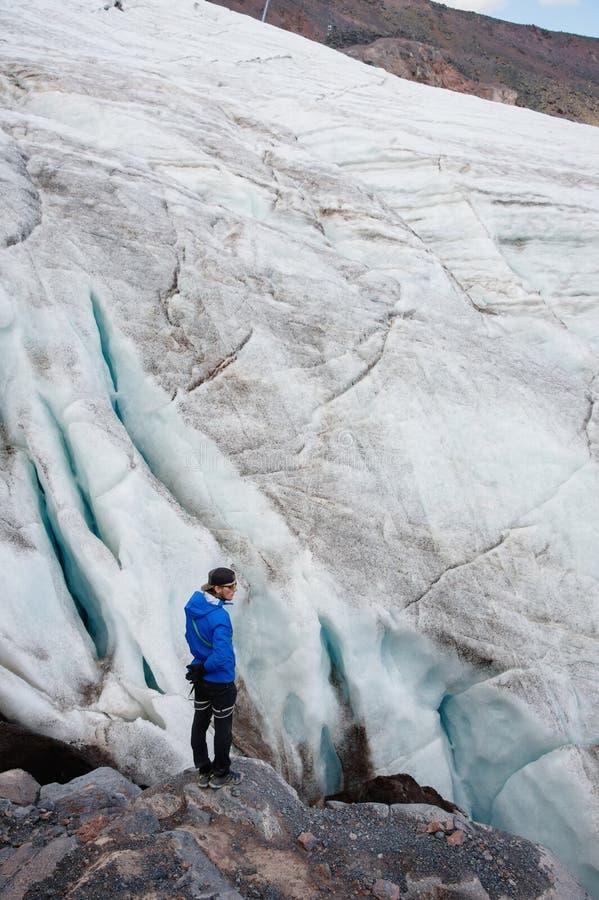 O viajante em um tampão e em óculos de sol está estando nas montanhas nevados na geleira Viajante em um ambiente natural fotografia de stock royalty free