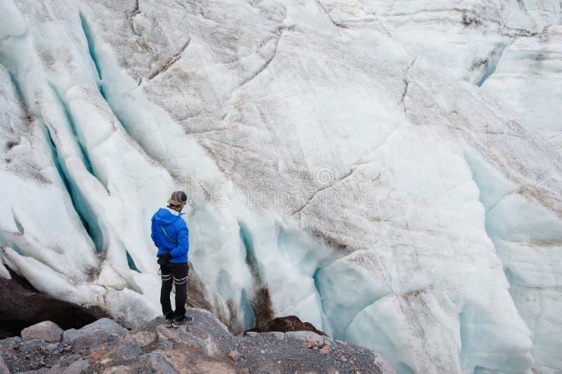 O viajante em um tampão e em óculos de sol está estando nas montanhas nevados na geleira Viajante em um ambiente natural fotografia de stock