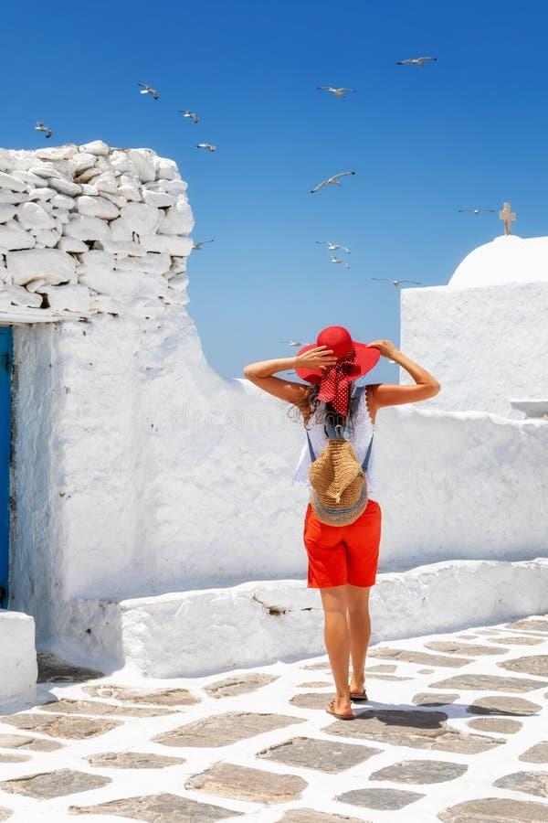 O viajante fêmea aprecia o cenário das ilhas de Cyclades em Grécia imagem de stock