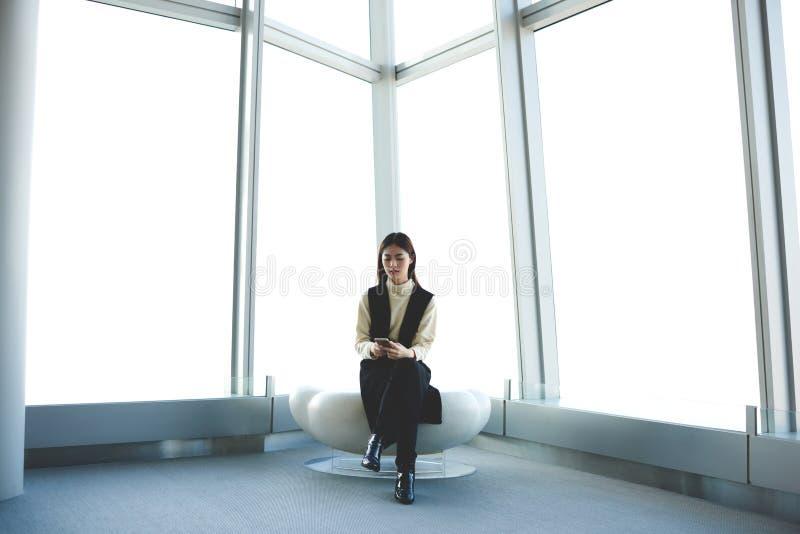 O viajante fêmea está usando o telefone esperto quando esperar o voo da partida no salão do aeroporto fotos de stock