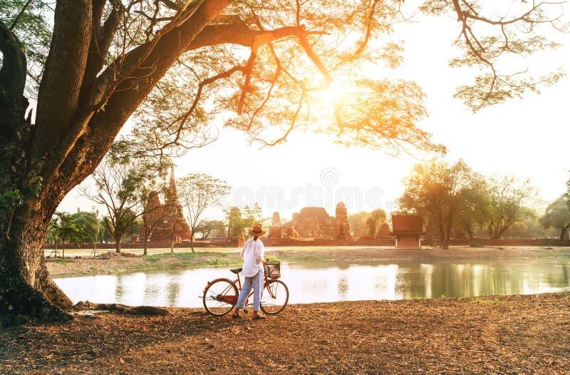 O viajante f?mea weared a roupa leve do ver?o e o chap?u tem a caminhada do amanhecer com a bicicleta perto da lagoa no parque hi fotografia de stock