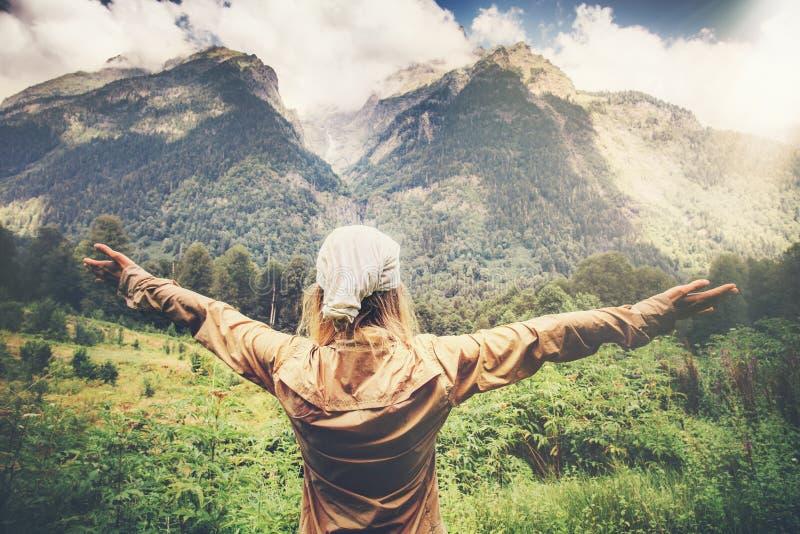 O viajante feliz da mulher entrega aumentado apreciando montanhas fotos de stock royalty free