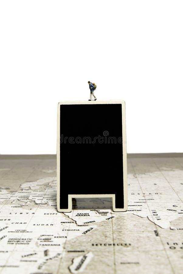 O viajante minúsculo de passeio modela sobre a placa preta vazia no mapa do mundo foto de stock royalty free