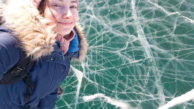 O viajante moreno de encantamento da menina toma um selfie que está no gelo brilhante claro do Lago Baikal Curso a Sibéria foto de stock royalty free