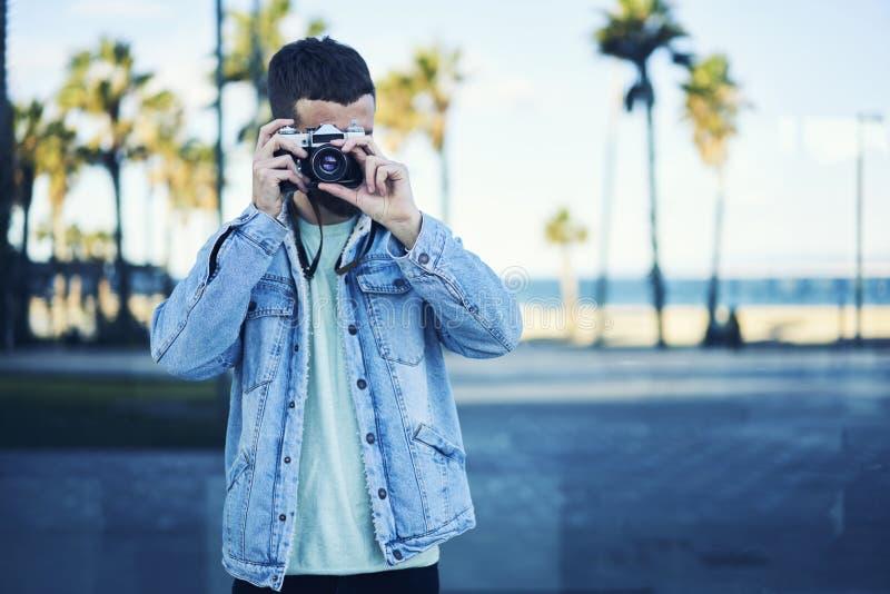 O viajante novo do blogger do moderno em um revestimento da sarja de Nimes transporta a atmosfera do litoral com palmeiras que dá imagem de stock royalty free