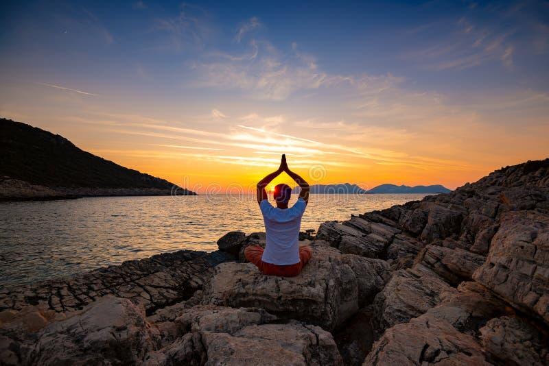 O viajante senta-se no litoral da rocha e na ioga praticando durante o por do sol fotografia de stock royalty free