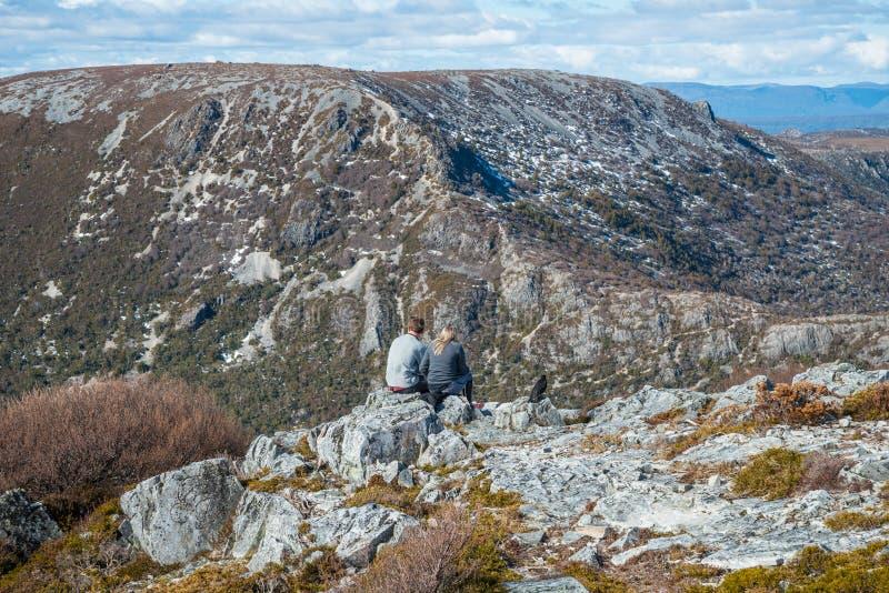 O viajante toma um resto na borda da montanha no parque nacional da montanha do berço do estado de Tasmânia de Austrália imagem de stock
