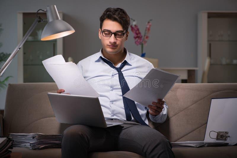 O viciado em trabalho do homem de negócios que trabalha tarde em casa fotos de stock royalty free