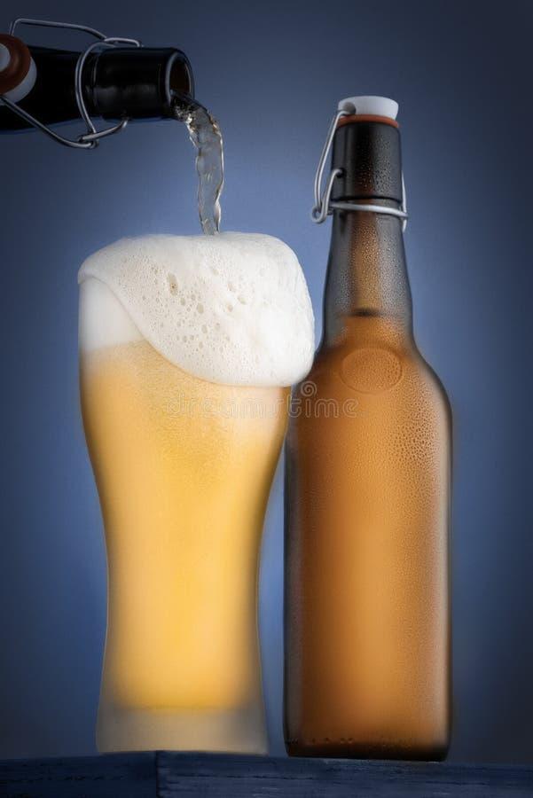 O vidro é cerveja fria derramada e uma garrafa do close-up da cerveja em um fundo azul Espuma sobre a borda em um vidro fotos de stock royalty free