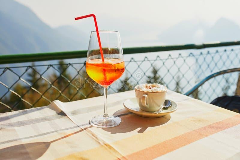 O vidro com aperol do cocktail spritz e x?cara de caf? com vista c?nico foto de stock
