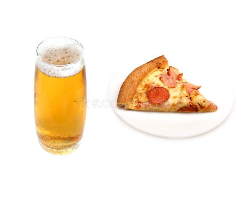O vidro com cerveja ambarina fria e a pizza remendam em uma placa isolada fotografia de stock royalty free