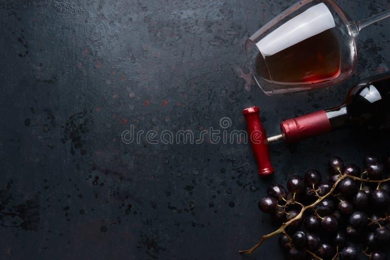 O vidro com vinho tinto, garrafa com corkscrew e a uva vermelha aglomera-se no fundo rústico preto, vista superior lugar para seu imagens de stock