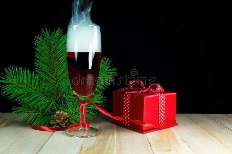O vidro de ano novo do vinho com árvores e presentes de Natal em um fundo escuro fotografia de stock