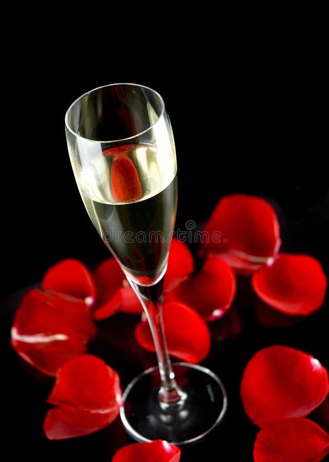 O vidro de Champagne com as pétalas de levantou-se imagem de stock royalty free