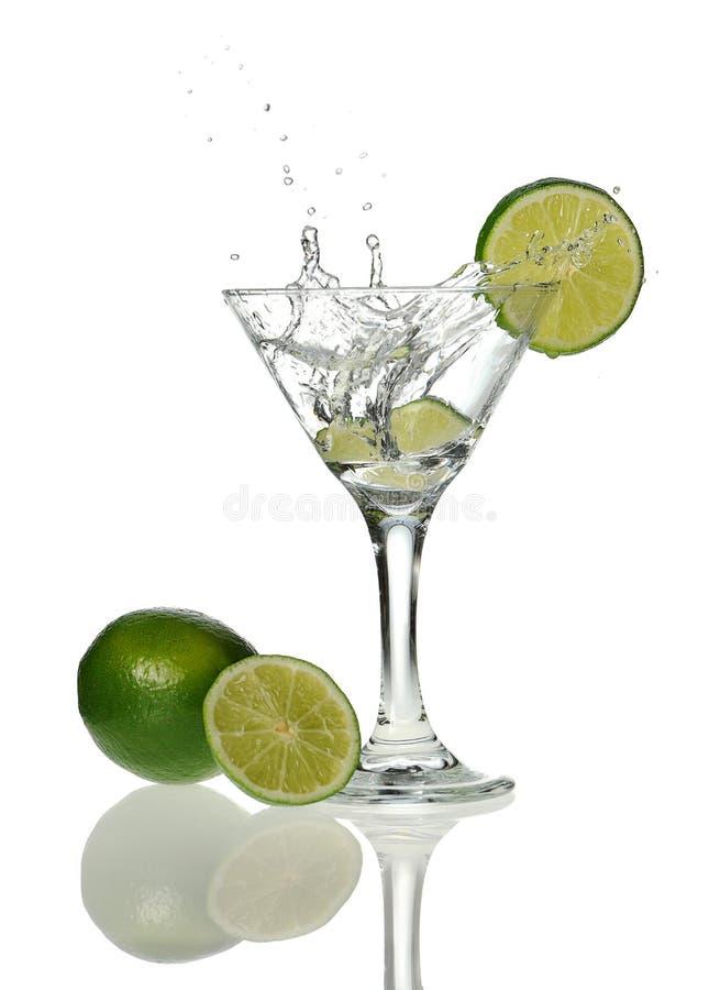 O vidro de Martini com a cunha do limão droped foto de stock
